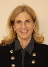 Headshot of Kim Stange-Hurlihy, smiling at the camera with tan background